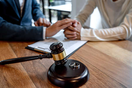 Contract decree of divorce (dissolution or cancellation) of marriage, husband and wife during divorce process and signing of divorce contract, Wedding ring. Фото со стока