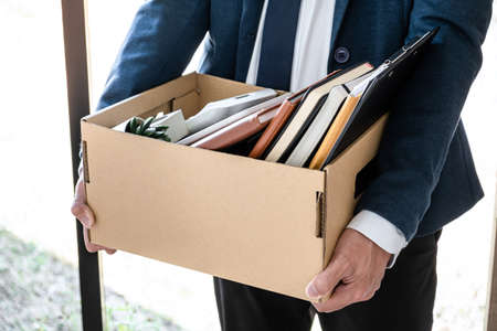 Images of businessman carrying packing up all his personal belongings and files into a brown cardboard box has frustrated and stressed to resignation and signing cancellation contract letter.