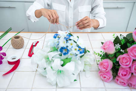 Arranging artificial flowers decoration at home, Young woman florist work making organizing diy artificial flower, craft and hand made concept. Stockfoto