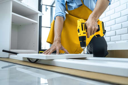 Man doing renovation work at home drilling wood with drill tack on locker. Stockfoto