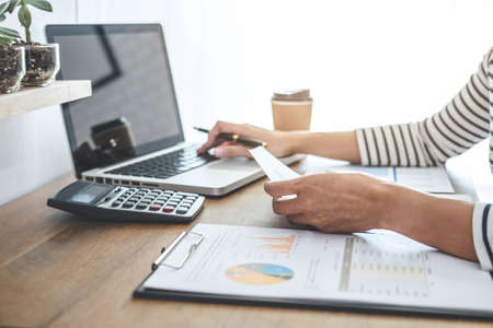 Female accountant calculations, audit and analyzing financial graph data with calculator and laptop Business, Financing, Accounting, Doing finance, Economy, Savings Banking Concept.