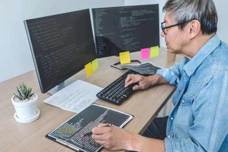 Programmeur professionnel senior travaillant au développement de la programmation et du site Web travaillant dans un bureau de développement de logiciels, écrivant des codes et tapant du code de données.