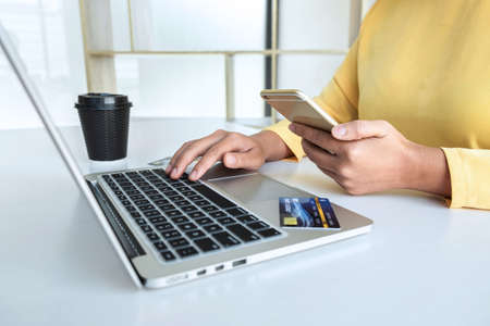 Woman using credit card and smartphone register security code payments online shopping and customer service network connection market, using technology on laptop, Internet Online shopping concept. Imagens
