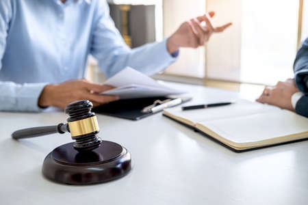 Consultation and conference of professional businesswoman and Male lawyers working and discussion having at law firm in office. Concepts of law, Judge gavel with scales of justice.