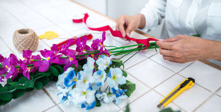 Arranging artificial flowers decoration at home, Young woman florist work making organizing diy artificial flower, craft and hand made concept. Stock Photo