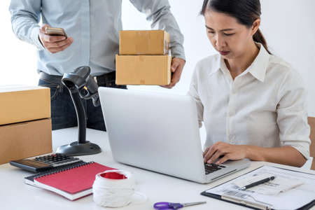 Young entrepreneur SME receive order client and working with packaging sort box delivery online market on purchase order and preparing package product, Small business parcel for shipment.