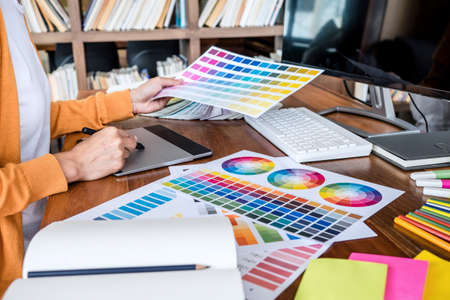 Image of female creative graphic designer working on color selection and drawing on graphics tablet at workplace with work tools and accessories. Stock fotó