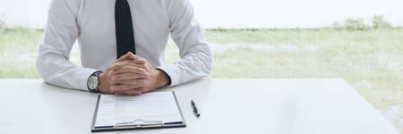 Interviewer or Board reading a resume during a job interview, Employer interviewing a young male job seeker for recruitment talking in modern office, employment and recruitment concept.