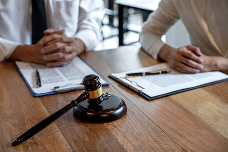Judge gavel and two golden marriage ring, Contract decree of divorce (dissolution or cancellation) of marriage, husband and wife during divorce process and signing of divorce contract.
