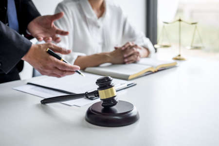 Consultation and conference of professional businesswoman and Male lawyers working and discussion having at law firm in office. Concepts of law, Judge gavel with scales of justice. Фото со стока
