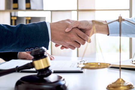 Handshake after good cooperation, Businesswoman Shaking hands with Professional male lawyer after discussing good deal of contract in courtroom, Concepts of law, Judge gavel with scales of justice.