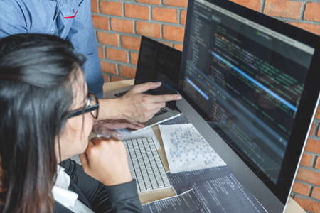 Programmers cooperating at Developing programming and website working in a software develop company office, writing codes and typing data code, Programming with HTML, PHP and javascript. Standard-Bild