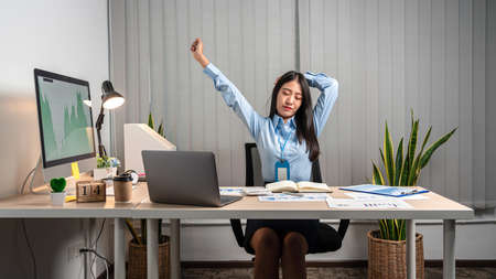 Young Asian Business woman sitting on the chair stretching herself and exercise for relaxation while working hard at office. Stockfoto