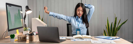 Young Asian Business woman sitting on the chair stretching herself and exercise for relaxation while working at office.