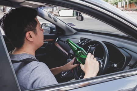 Young asian man drives a car with drunk a bottle of beer behind the wheel of a car. Foto de archivo