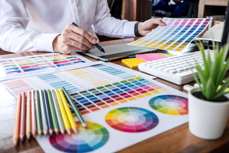 Image of male creative graphic designer working on color selection and drawing on graphics tablet at workplace with work tools and accessories.