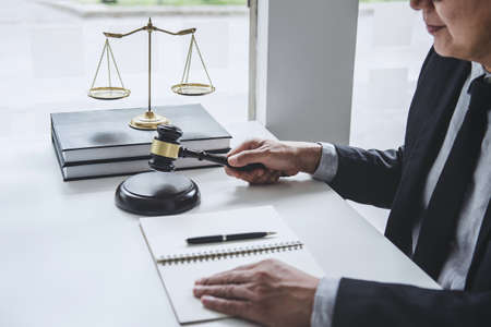 Judge gavel with Justice lawyers, Counselor in suit or lawyer working with contract papers on a documents in courtroom, Legal law, advice and justice concept.