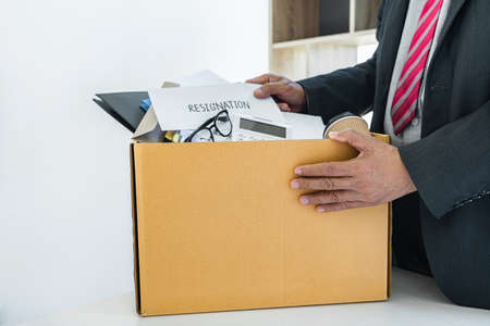 Businessman carrying packing up all his personal belongings and files into a brown cardboard box to resignation in modern office, resign concept.