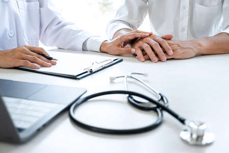 Image of doctor touching patient hand for encouragement and empathy on the hospital, cheering and support patient, Bad news, medical examination, trust and ethics.