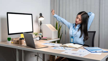 Young Asian Business woman sitting on the chair stretching herself and exercise for relaxation while working hard at office. Imagens
