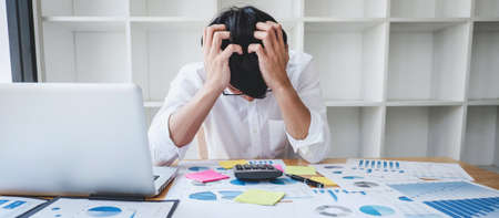 Image of Frustrated stressed businessman and graph document with computer laptop in the workplace.