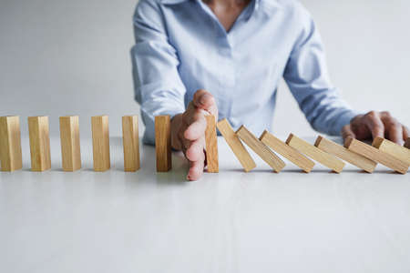 Risk and strategy in business, Close up of business woman hand stopping wooden block between three way from falling in the line of domino. Stock Photo