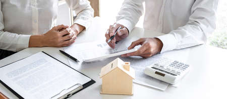 Real estate broker agent presenting and consult to customer to decision making sign insurance form agreement, home model, concerning mortgage loan offer for and house insurance. Imagens