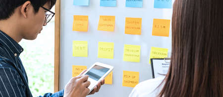 Two creative Business people meeting and planning use sticky note on board to share idea, Analysis data charts and graph with teamwork strategy brainstorming. 版權商用圖片 - 158273999