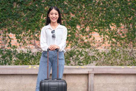 Smiling woman traveler dragging black suitcase luggage bag walking to passenger boarding in airport, Travel concept. 版權商用圖片