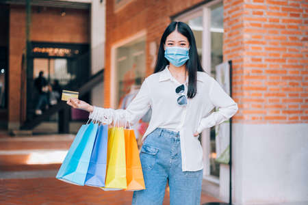 Portrait of Asian girl excited beautiful girl wearing protective mask happy smiling with holding credit card and shopping bags enjoying in shopping relaxed expression, lifestyle concept.