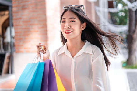 Portrait of Asian girl excited beautiful girl wearing sunglasses happy smiling with holding shopping bags enjoying in shopping relaxed expression, Positive emotions shopping, lifestyle concept. Standard-Bild