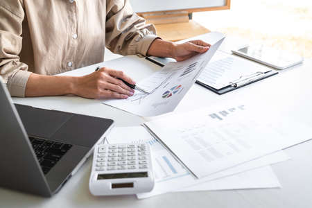 Professional at work, business woman working and analyzing on laptop with calculate statistics of financial document data graph for new project of business strategy and market growth at workplace.