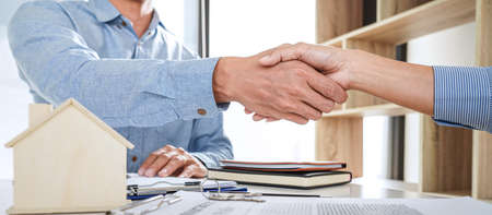 Real estate agent and customers shaking hands together celebrating finished contract after signing about home insurance and investment loan, handshake and successful deal. Standard-Bild