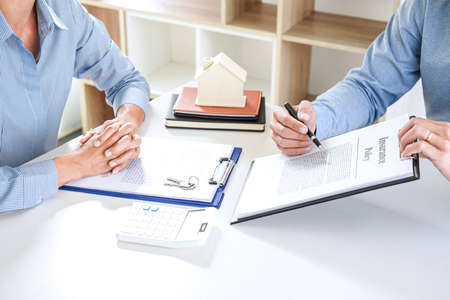 Real estate broker agent consult to customer to decision making sign insurance form and sending house model to client after approve, home model mortgage loan offer for and house insurance.