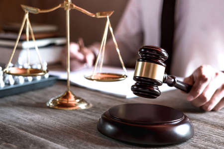Gavel on wooden table and Lawyer or Judge working with agreement in Courtroom theme, Justice and Law concept.