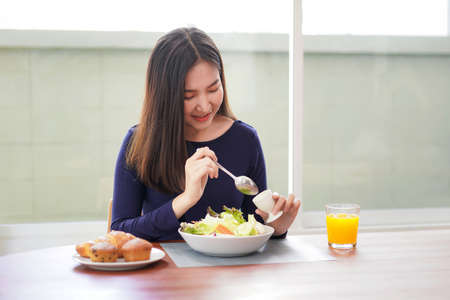 Young asian woman eating healthy salad with fresh vegetable and orange juice on wellness lifestyle for breakfast with healthy meal at home