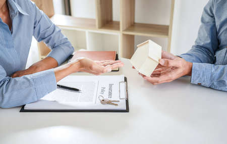Real estate Sales manager giving keys and house model to customer after signing rental lease contract of sale purchase agreement, concerning mortgage loan offer for and house insurance.