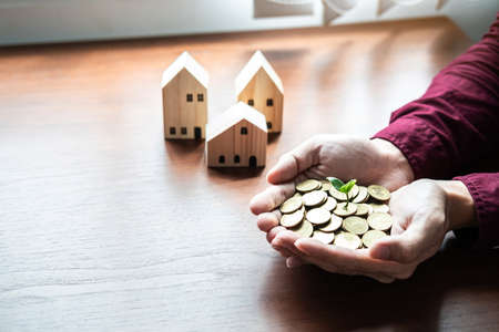 Plant sprouting growing on pile of coins in hands asian businessman with house model on table to saving money for buy house or real estate in risk investment