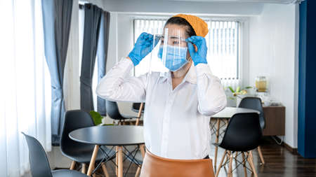 Asian woman waitress in medical glove to wearing face mask and face shield to prevent and stop coronavirus before working for the service provided to customers in restaurant