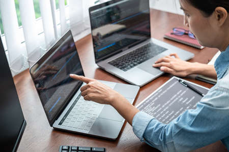 Asian programmer woman pointing and looking on multiple laptop screen to writing code and database while working about development website or applications in software development office Archivio Fotografico