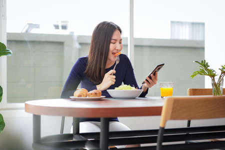 Young asian woman eating healthy salad with fresh vegetable on wellness lifestyle and looking on smartphone while breakfast with healthy meal at home