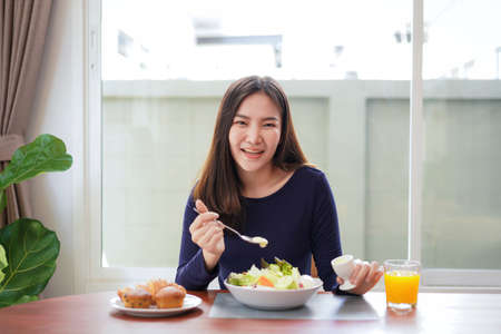Young asian woman use a salad dressing spoon to mixing with fresh vegetable on wellness lifestyle while looking at the camera and breakfast with healthy meal at home