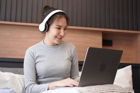 Young asian woman with headphone put laptop on pillow to typing business project and checking social media apps while relaxing by listening to music and sitting on the bed in home bedroom