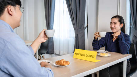 Young asian business couple drinking coffee and bread to celebrate after job success while sitting with table shield plastic partition to protect from coronavirus at restaurant or cafe 版權商用圖片