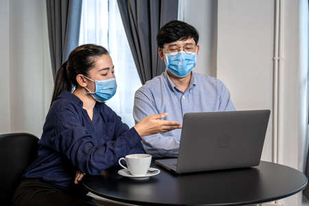 Young asian business couple looking business data on laptop to brainstorming new project while wearing protective face mask to protection from coronavirus at restaurant or cafe