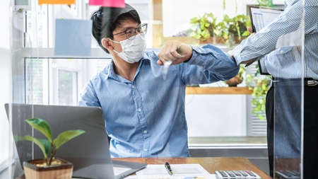 Two business colleagues avoid handshake greeting each other by bumping elbows when meeting in office while wearing face mask to protect infection from coronavirus covid-19 and social distancing
