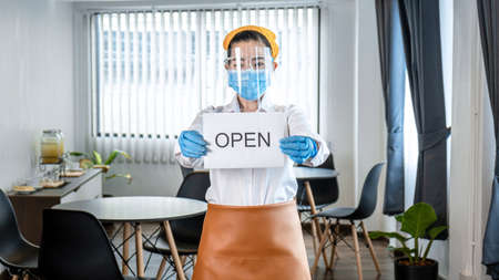 Asian woman waitress wearing protective face mask and medical glove to holding open sign for welcoming client while standing in restaurant after lockdown quarantine