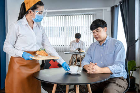 Asian woman waitress serving coffee and bread to client while wearing face mask and face shield with medical gloves to protect infection from coronavirus in cafe