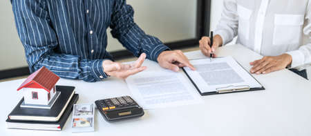 Real estate broker agent being analysis and making the decision a home estate loan to customer to signing contract documents for realty purchase, Bank employees recommend mortgage loan approval.