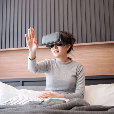Close up of young asian woman in casual clothes raising hand to touching the air and wearing virtual reality glasses while rest and sitting on the bed in home bedroom